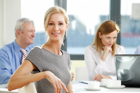 Portrait of attractive smiling businesswoman sitting at meeting while business people sitting at background and working on business report. Teamwork at office.